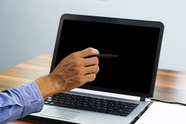 Hand pointing focus on computer in workspace office