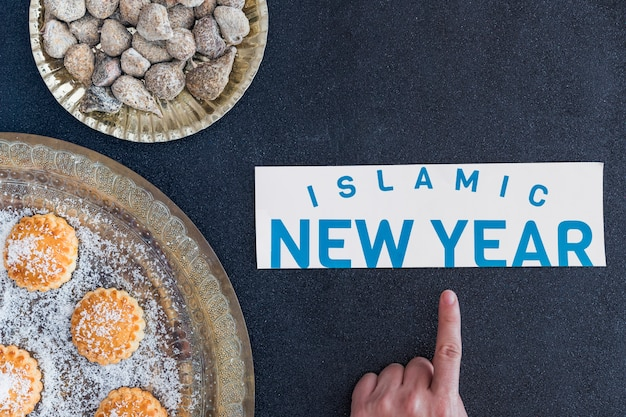 Hand pointing at islamic new year at desserts
