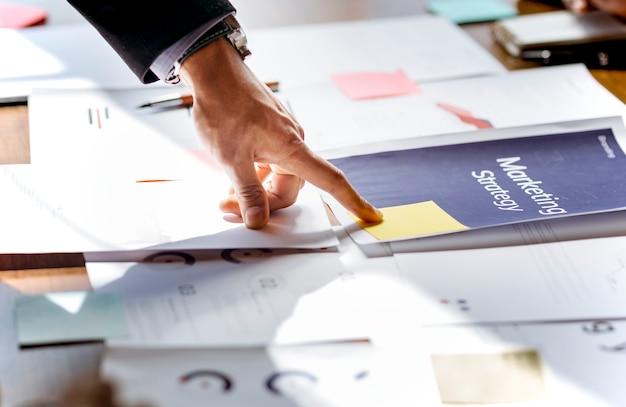 Рука, указывающая на документ маркетинговой стратегии