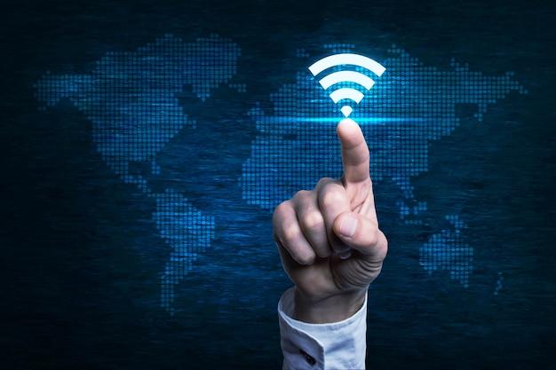 Рука, указывающая на кнопку wi-fi над цифровой картой мира