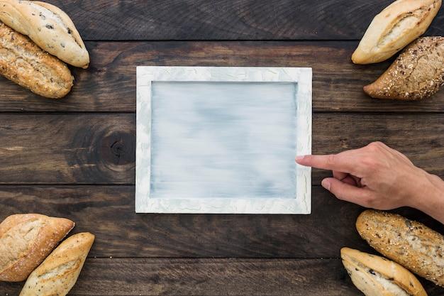 Hand pointing at tray near bread loafs