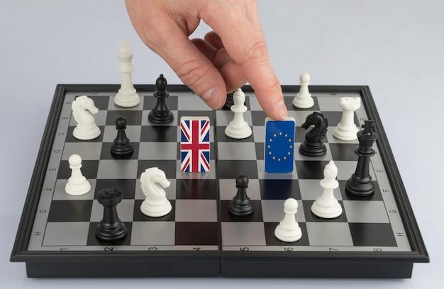 Рука политика поднимает фигуру с флагом европейского союза политическая игра и стратегия