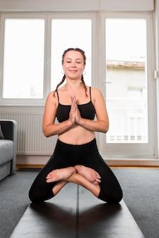 Posizione della mano a praticare yoga a casa concetto Foto Gratuite