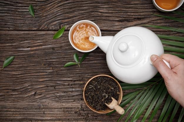 ティーポットからカップに熱い蒸し茶を手で注ぎ、木製のテーブルの上に乾燥ハーブティーを空にして創造的なフラットレイアウト、伝統的なスタイルで健康的な自然のオーガニック製品