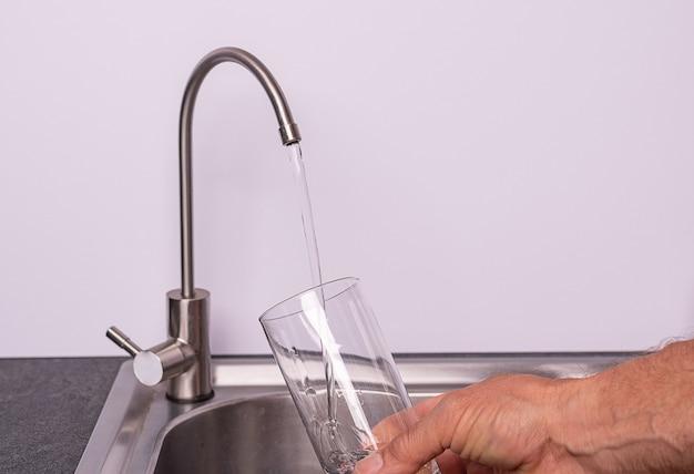 필터 탭, 흰 벽, 복사 공간에서 물 한 잔을 붓는 손