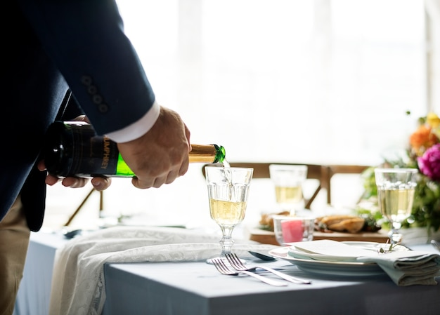 Hand pouring champagne in a glass