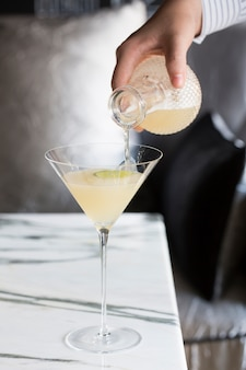 Hand pouring cocktail into  glass