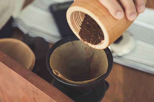 A hand pouring coffee from wooden grinder into filter