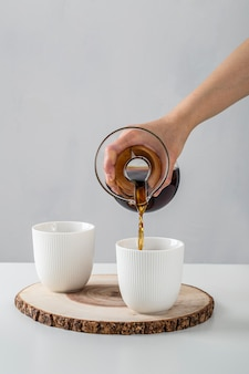 Hand pouring coffee into mugs on table