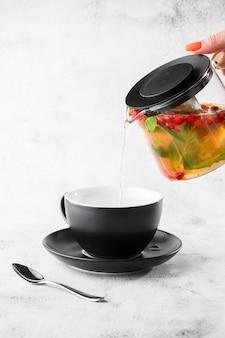 大理石の背景に分離された黒のカップにガラス小さじからクランベリー、オレンジ、ミントまたは黄色いお茶を注ぐ手。俯瞰、コピースペース。カフェメニューの宣伝。コーヒーショップメニュー。垂直