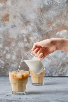ロックグラスのアイスコーヒーにクリームを手で注ぐ