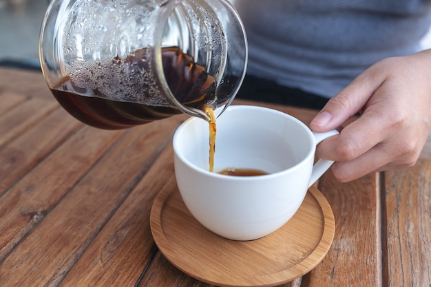 ヴィンテージの木製テーブルの白いマグカップにドリップコーヒーを手で注ぐ