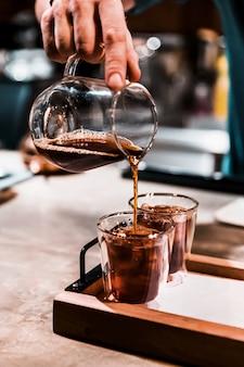 ショットグラスにエスプレッソコーヒーを注ぐ手