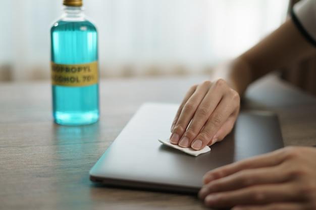 Рука наливает этиловый спирт из бутылки в кусок хлопка для чистого ноутбука