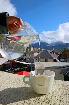 コーカサス山脈を背景にしたポータブルドリップコーヒーバッグに手でお湯を注ぐ