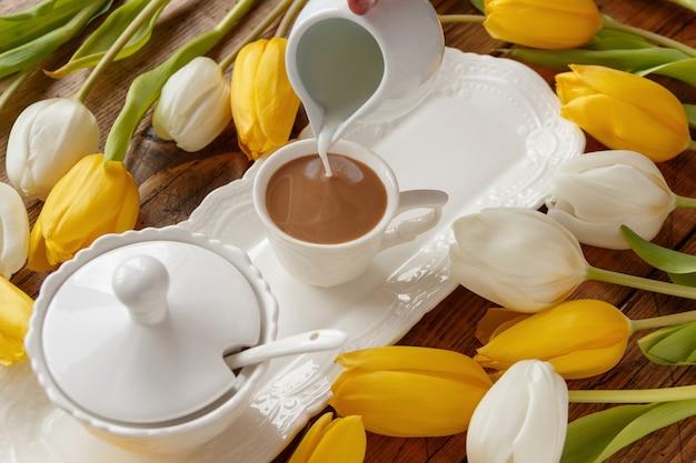 木製のテーブルの白と黄色のチューリップの近くのコーヒーにミルクを手で注ぐ