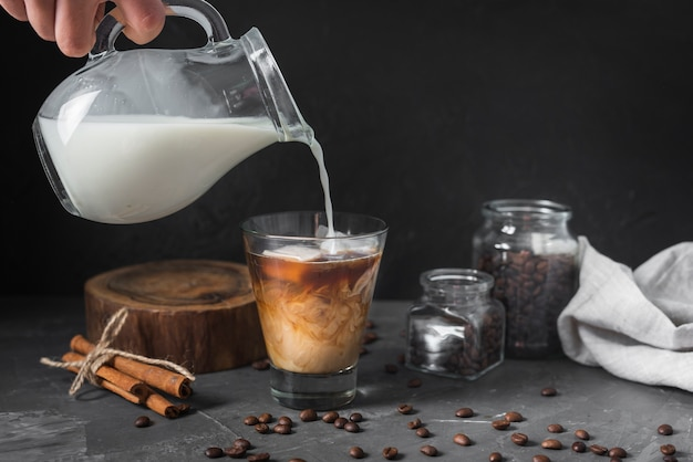Hand pouring milk into glass with coffee