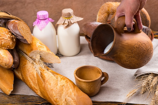 Hand pouring milk into wooden cup surrounded by bottles, loaves of bread and wheat stalks over wooden table background