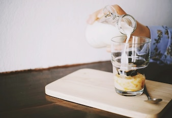 Hand pouring milk to glass on iced espresso with copy space