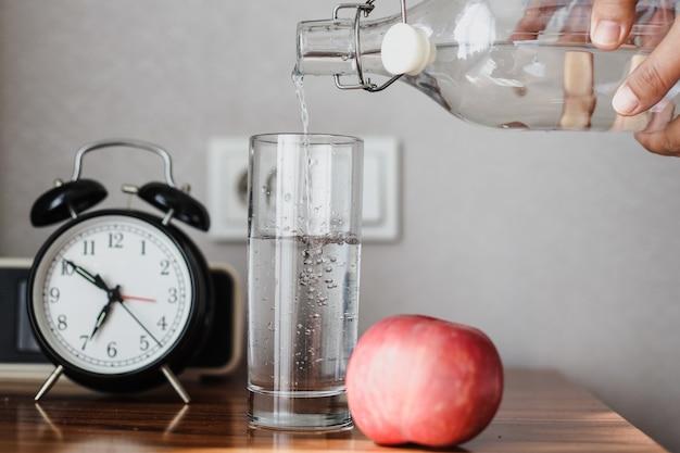 Рука наливает минеральную воду из бутылки в стакан с яблоком на столе для концепции завтрака