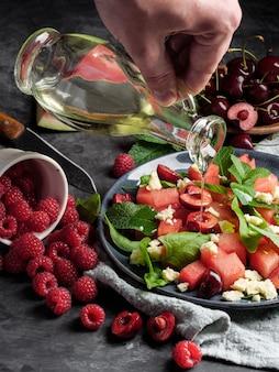 Рука поливает маслом салат с арбузом, сыром, мятой, ягодами и вишней на сером фоне