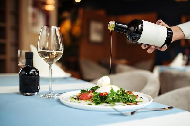 Рука наливает оливковое масло на итальянский салат буррата