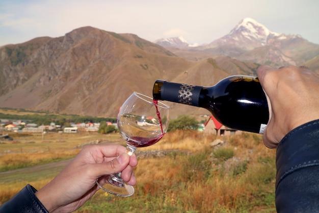 ぼやけたカズベック山を背景に、赤ワインをワイングラスに手で注ぐ、ゴルジア