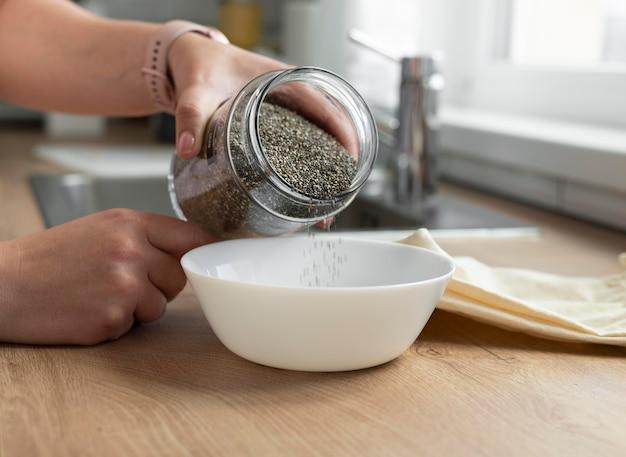 그릇에 손을 붓는 씨앗을 닫습니다.