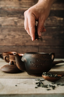 Hand pouring tea herbs in a teapot front view