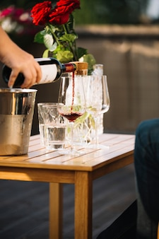 Hand pouring wine in transparent glass on wooden table