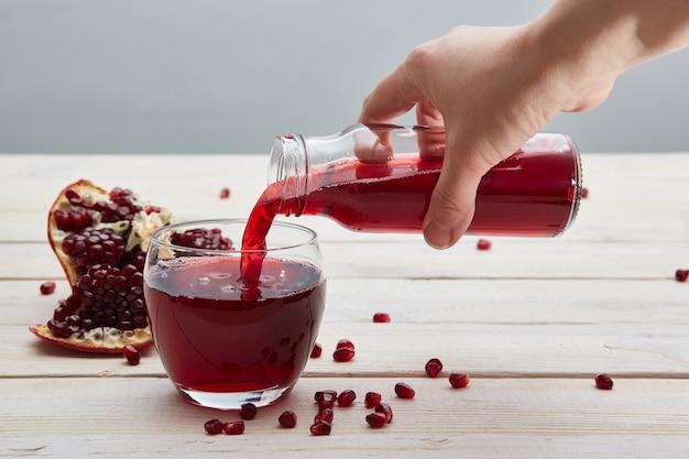 Рука наливает гранатовый сок из стеклянной бутылки в стакан. открытые гранаты и зерна на деревенском светлом столе