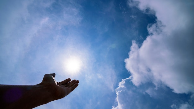 Hand praying for blessing from god on sun and clouds, christian religion concept