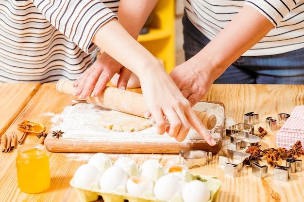 Рука готовит печенье из теста на кухне