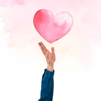 バレンタインのお祝いの水彩イラストの心を提示する手