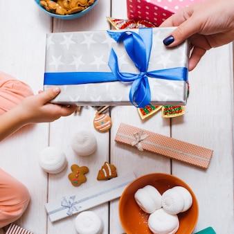 새 해 선물을 제시하는 손. 블루 리본으로 포장 된 상자