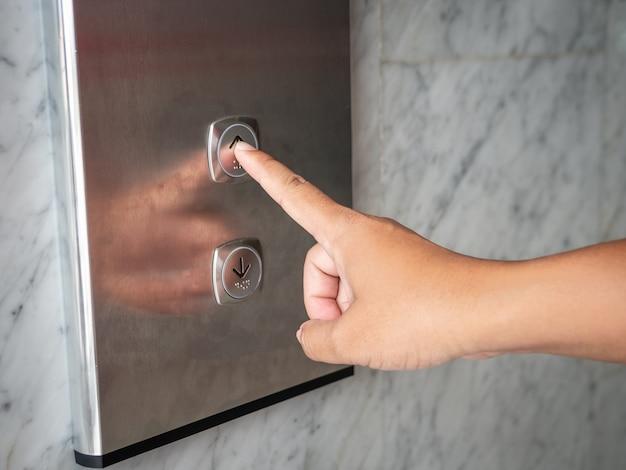 엘리베이터의 위로 버튼을 손으로 누르십시오