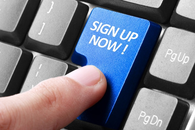 Hand press sign up now button on keyboard