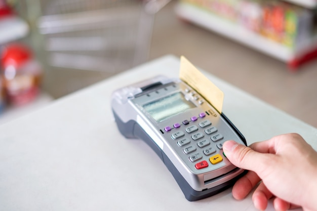 Hand press with swiping credit card on payment terminal in store
