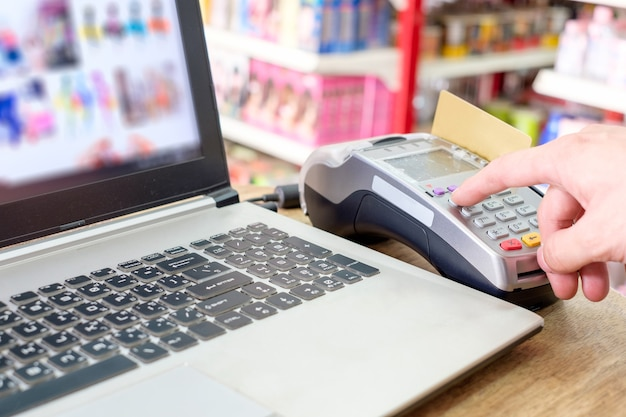 Hand press with swiping credit card on ternimal and using laptop payment shopping online