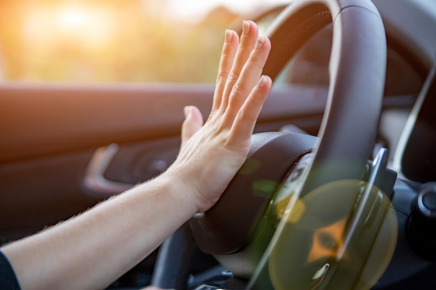 Hand presses the horn on the steering wheel of a modern car no face