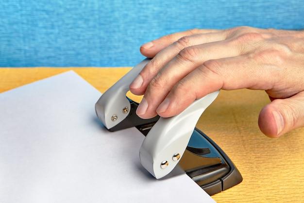 Рука нажимает дырокол, который проделывает дыры в листе бумаги.