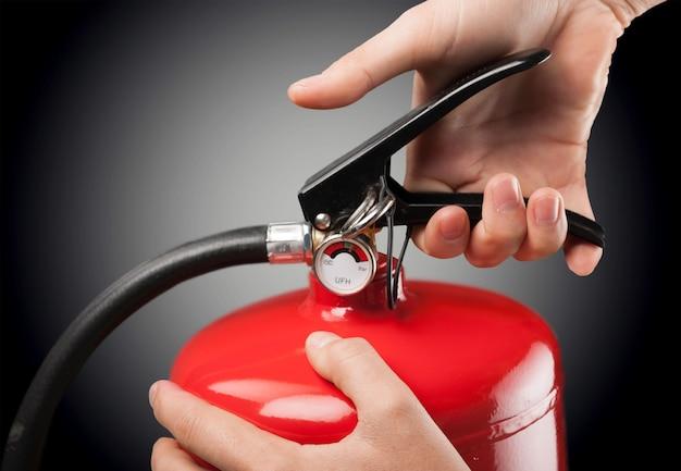 Рука нажимает на курок огнетушителя, рука нажимает на курок огнетушителя
