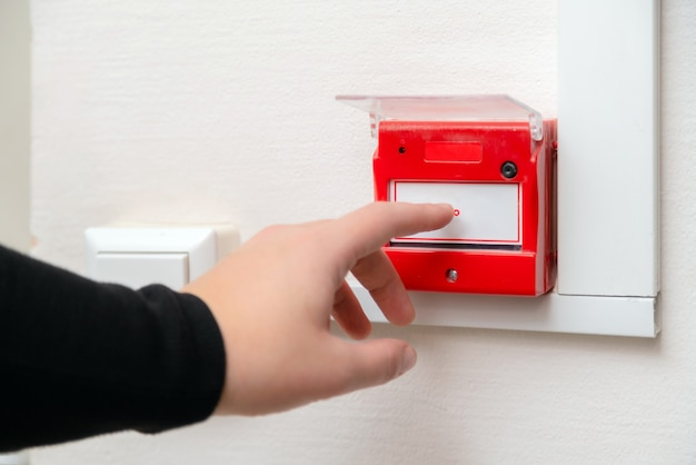 Hand pressing fire alarm button at school or business office.
