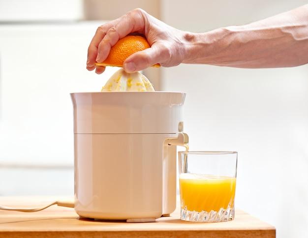 전기 과즙 짜는기구와 오렌지 과일을 눌러 수동으로