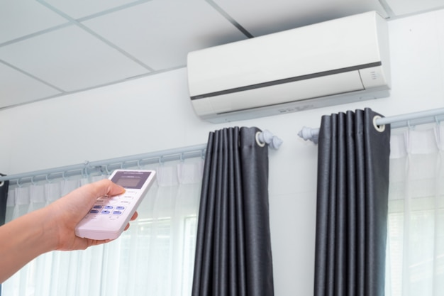 Hand pressing remote control air conditioner in room.
