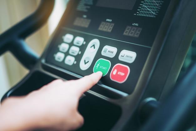 Hand pressing start on treadmill