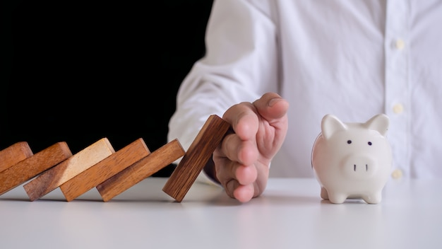 Hand preventing domino from falling into the piggy bank. prevention of external hazards. money insurance plan