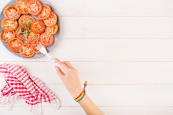Hand pricking tomato from plate