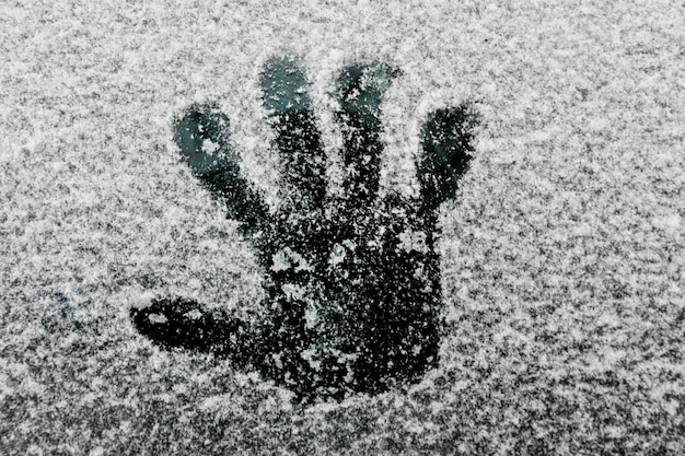 Hand print on glass in winter