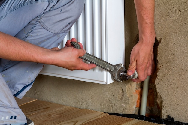 Hand of a professional plumber worker installing heating radiator on brick wall using a wrench in an empty room of a newly built apartment or house. construction, maintenance and repair concept.